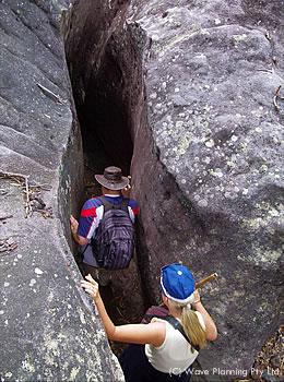 巨大な岩山の裂け目を身を反らせながらくぐり抜ける