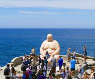 今年、一番人気の海に背を向けて座り込む太った人