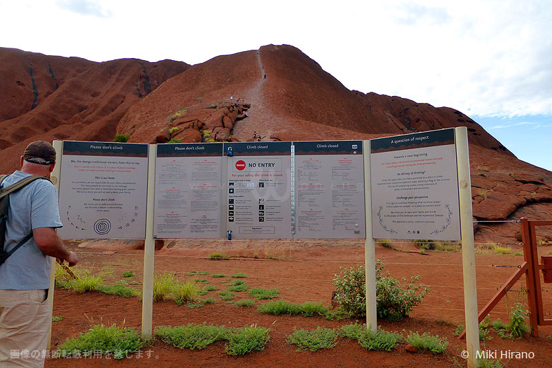 「登らないで」と書かれた看板に足を止める観光客