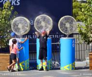 冷水ミストがでる扇風機の前で涼む子供たち